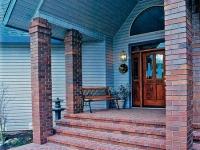 Большое крыльцо с кирпичными ступенями и колонами