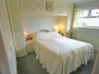 Встроенная мебель с навесными антресолями в малогабаритной спальне