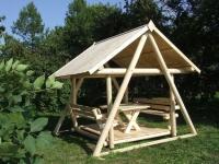 Маленькая бревенчатая беседка под деревянной крышей