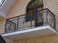 Кованые ограждения с перилами из дерева на балконе