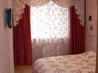 Шторы с мягким ламбрекеном из двух видов ткани на окнах спальни